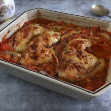 Baked chicken legs with tomato and oregano on a baking dish