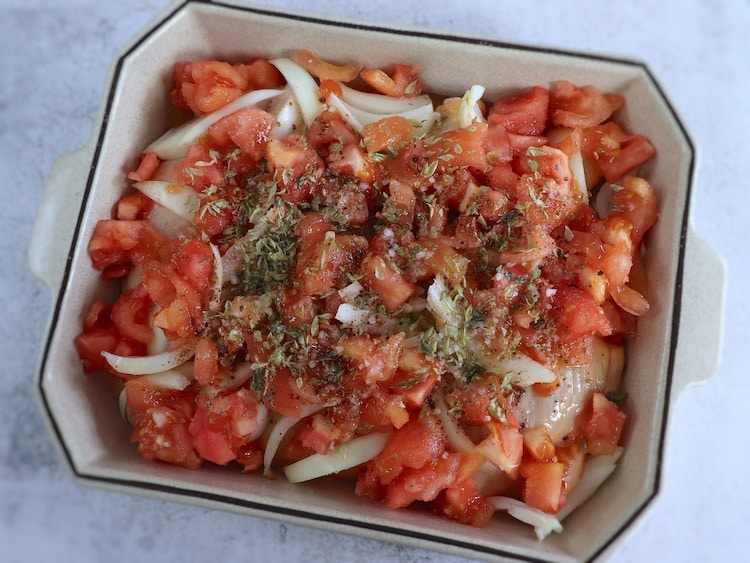 Chicken legs with tomato and oregano on a baking dish