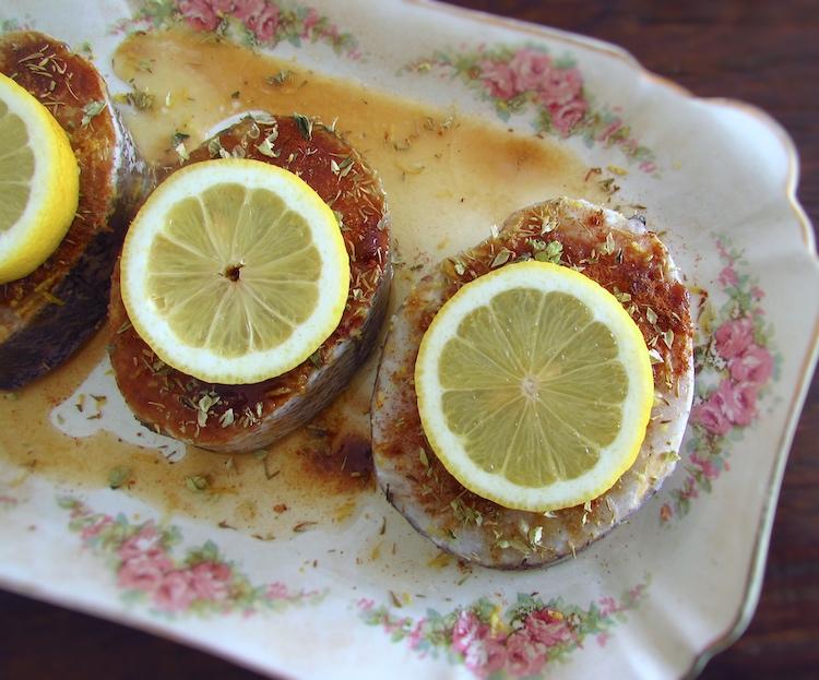 Pescada temperada com sal, açúcar mascavado escuro, canela, tomilho, raspa de limão, sumo de limão, rodelas de limão e orégãos