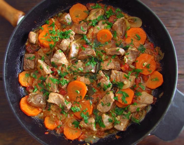 Carne de porco estufada com cenoura numa frigideira