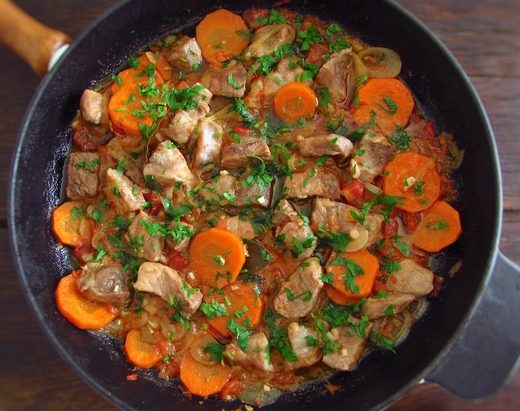 Stewed pork with carrot on a frying pan