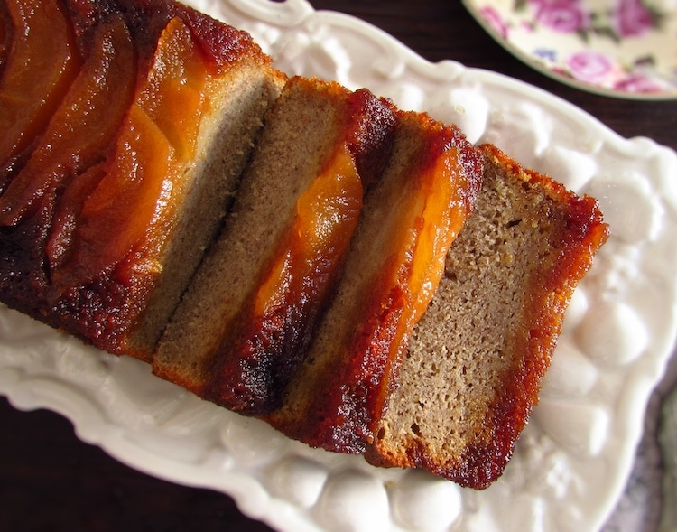 Banana cake with caramelized pear slices on a platter