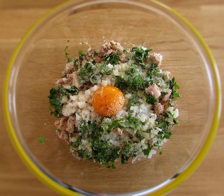Atum, cebola picada, a gema de ovo, coentros picados, uma pitada de sal, pimenta e o pão ralado numa taça de vidro