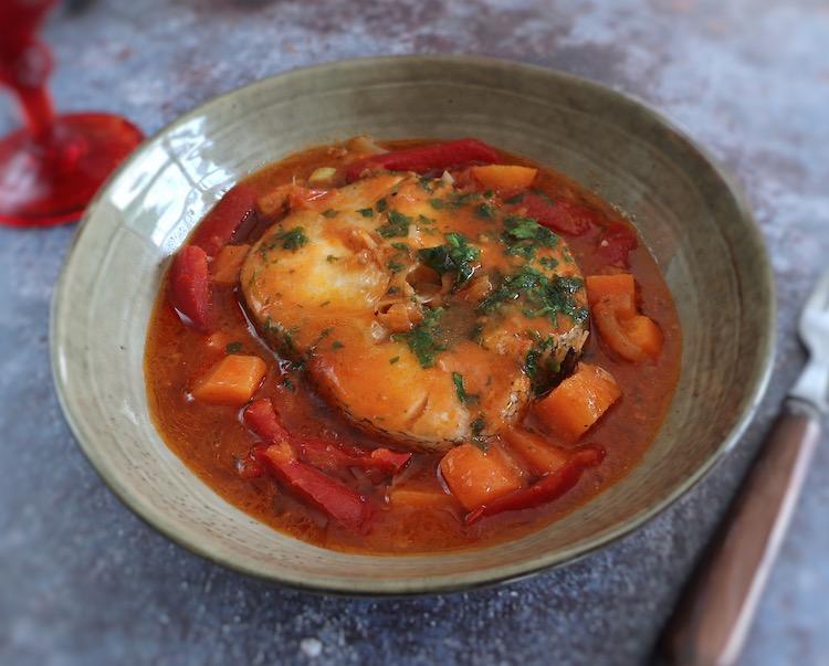 Peixe guisado com cenoura e pimento vermelho num prato fundo