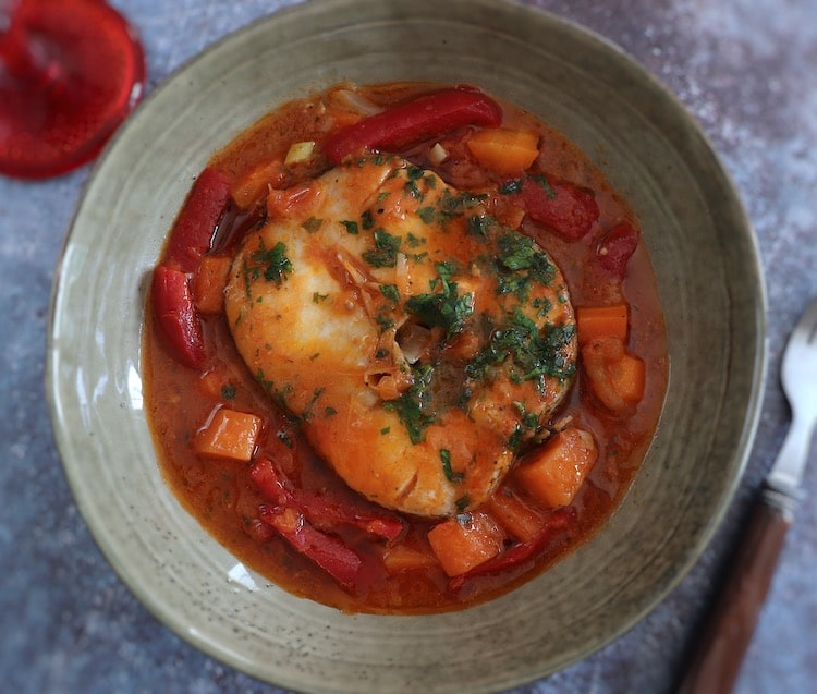 Simple fish stew with carrot and red pepper on a dish bowl