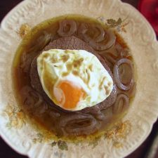 Stewed beef medallions with fried egg on a plate