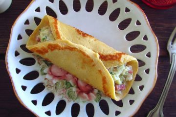 Crepes filled with cod and bacon on a plate