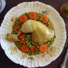 Coxas de frango estufadas com ervilhas e cenoura num prato