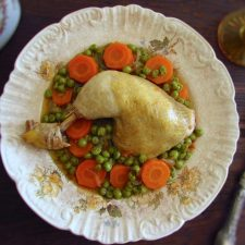 Stewed chicken legs with peas and carrot on a plate