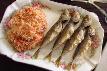 Carapaus fritos com arroz de tomate numa travessa
