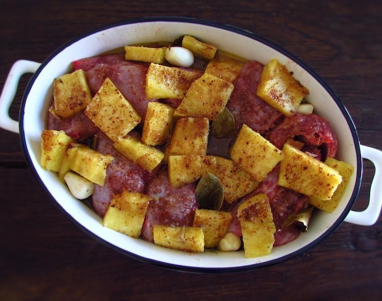 Coelho e ananás cortado em pedaços temperado com sal, noz-moscada, canela, mel, alhos descascados, louro e azeite