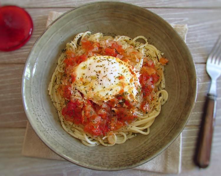 Esparguete com ovos escalfados em molho tomate num prato com um garfo
