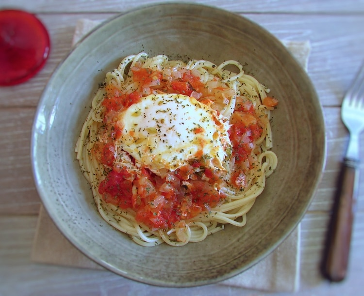 Esparguete com ovos escalfados em molho tomate num prato fundo
