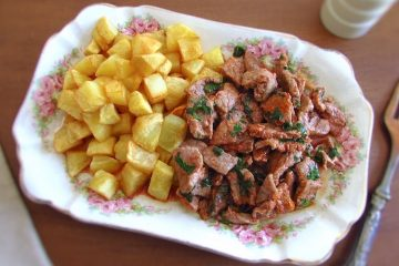 Bifes com batata frita numa travessa