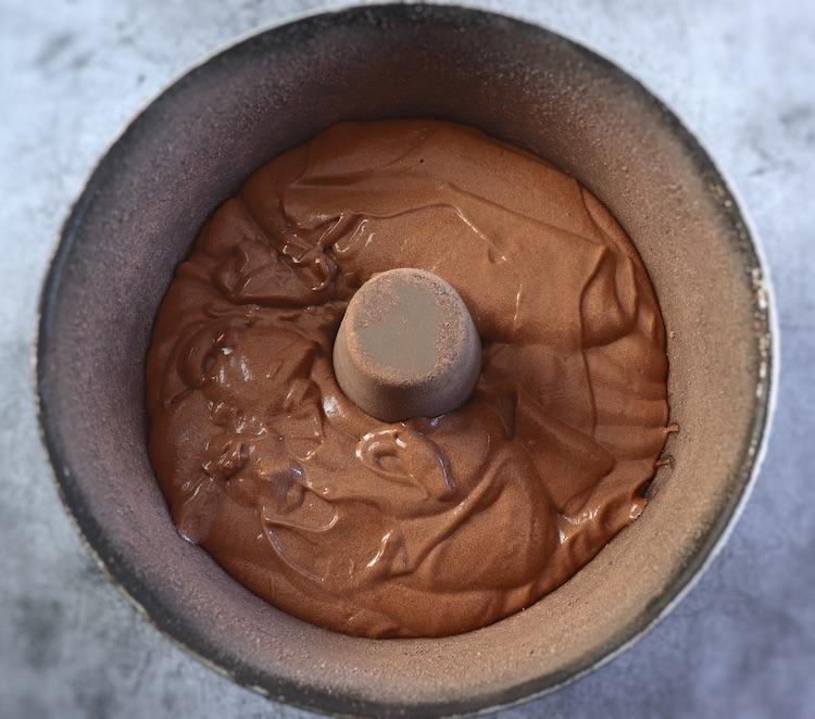 Massa de bolo de café e cacau numa forma de bolos redonda com furo no meio