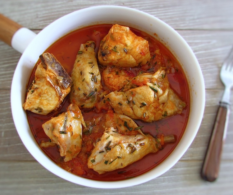 Chicken with tomato sauce and rosemary on a plate with a fork