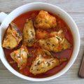 Frango com molho de tomate e alecrim num prato com um garfo
