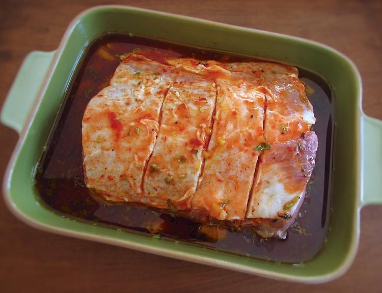 Lombo de porco numa assadeira temperado com sal, o azeite, os alhos descascados, o sumo de limão, a massa de pimentão, a pimenta, a noz-moscada, os orégãos, o molho Inglês e a mostarda