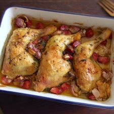 Chicken legs in the oven with chouriço and garlic on a baking dish