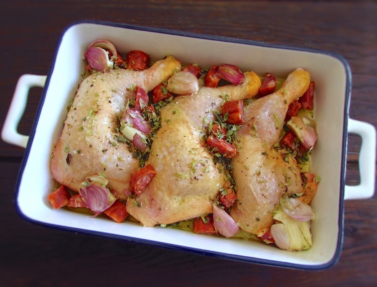 Chicken legs with chouriço and garlic on a baking dish