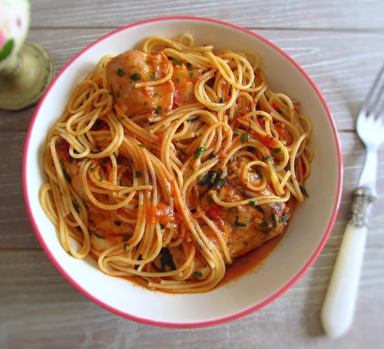 Coelho guisado com esparguete num prato com um garfo
