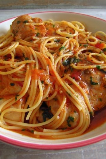 Stewed rabbit with spaghetti on a plate with a fork