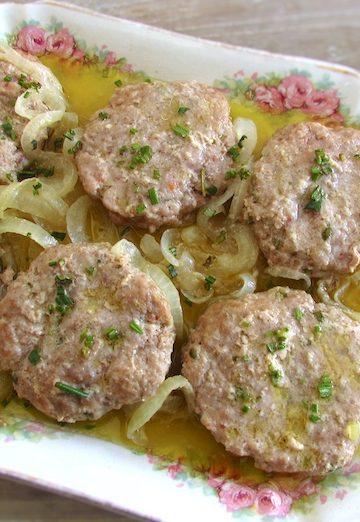 Hambúrgueres estufados com alecrim numa travessa com um garfo