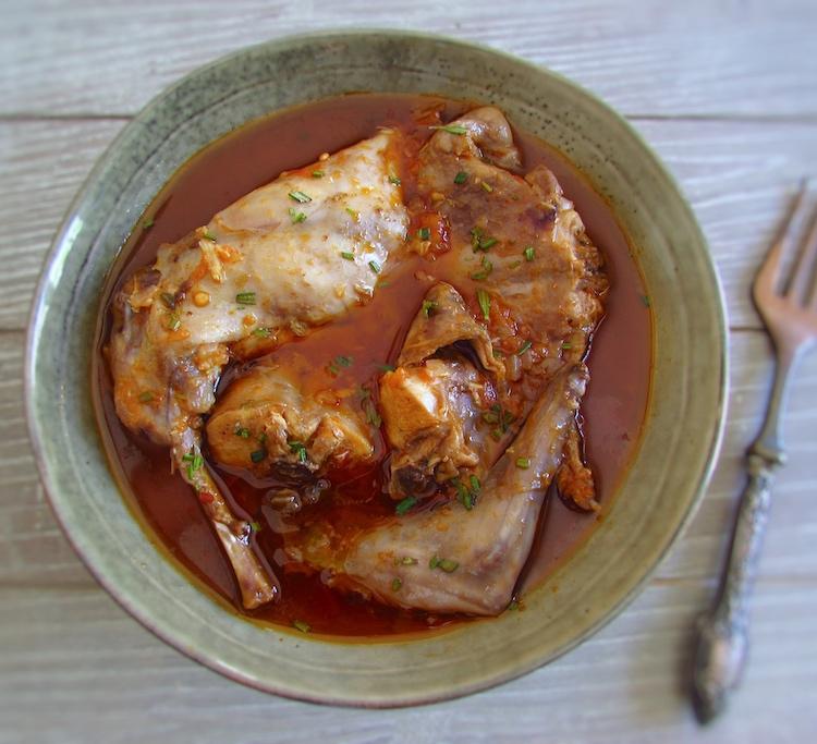 Coelho guisado com especiarias num prato com um garfo