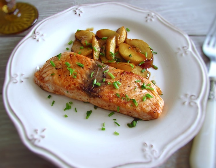 Salmon with caramelized apple on a plate with a fork