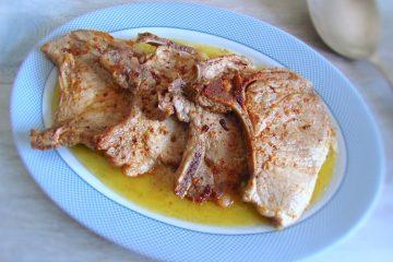 Costeletas de porco fritas numa travessa com uma colher