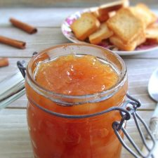 Pear and honey jam in a glass jar with toasts and cinnamon sticks