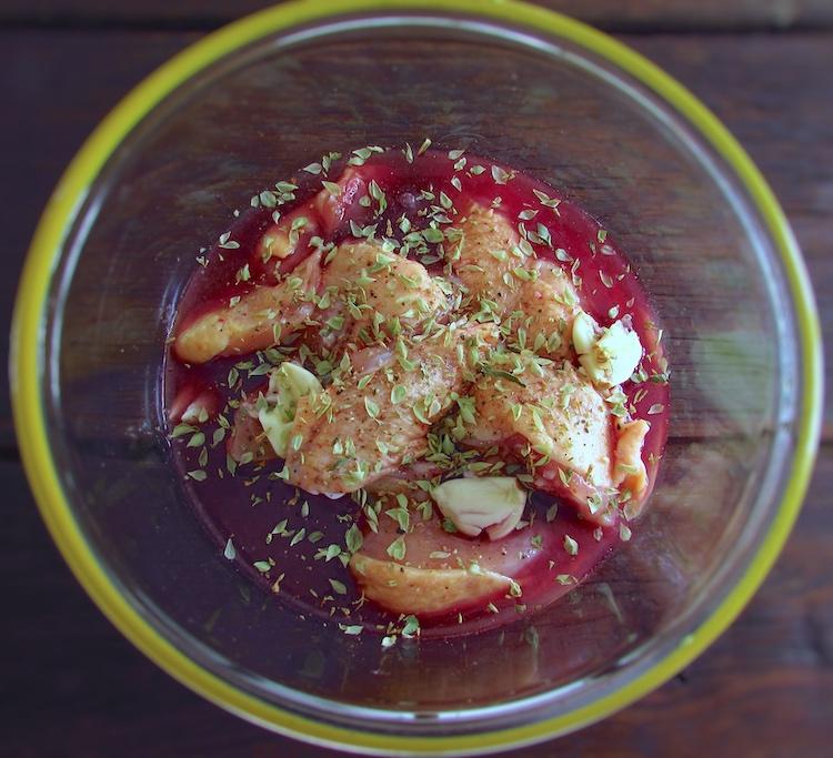 Frango temperado com sal, alhos esmagados, pimenta, vinho tinto, vinho branco e orégãos numa tigela de vidro