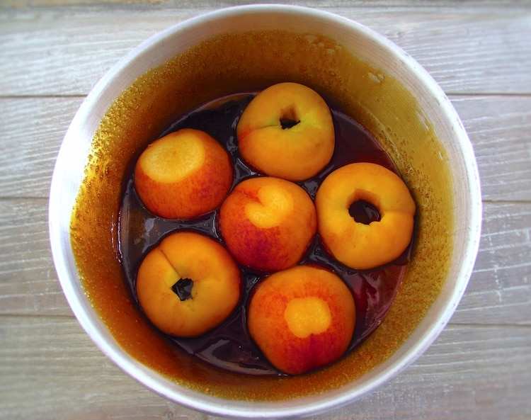 Peach halves caramelized with sugar on a round cake pan