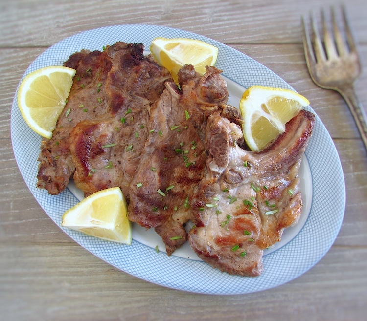 Grilled chops with lemon and rosemary on a platter