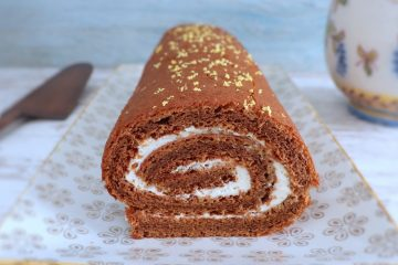 Roll cake filled with whipped cream on a rectangular plate