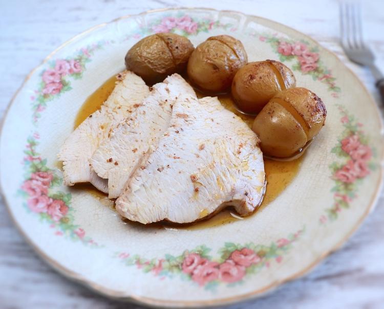 Fatias de lombo de peru com batatas no forno num prato