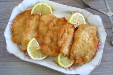 Breaded chicken steaks on a platter