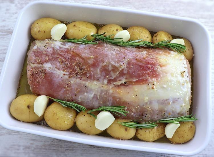 Lombo de porco e batatas numa assadeira temperados com sal, pimenta, alhos descascados, sumo de limão, azeite, mel e alecrim