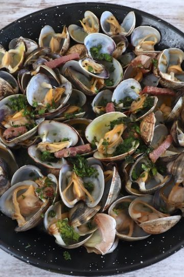 Clams with bacon and garlic on a frying pan