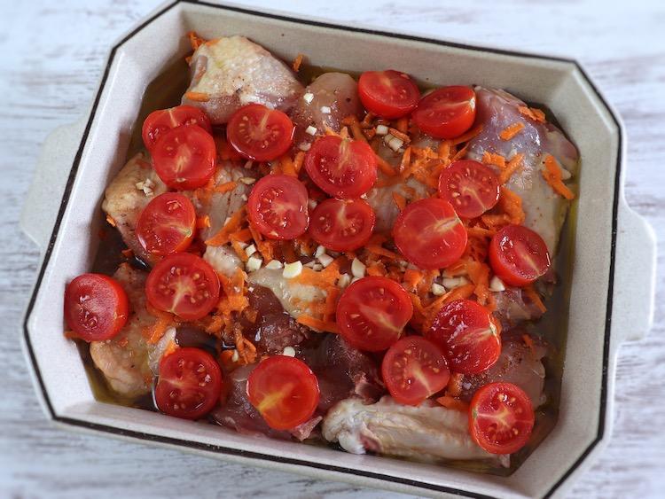 Frango temperado com tomate cherry e cenoura numa assadeira