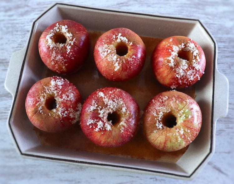 Apples on a baking dish seasoned with cinnamon powder, orange juice, Port wine and yellow sugar