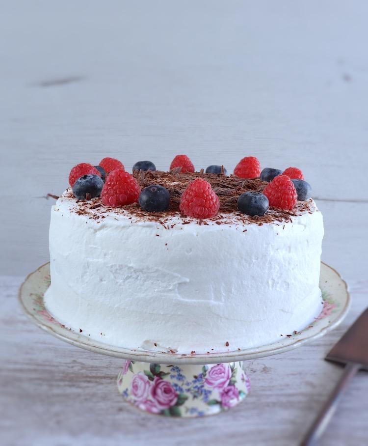 Bolo de cacau com chantilly e frutos vermelhos num prato