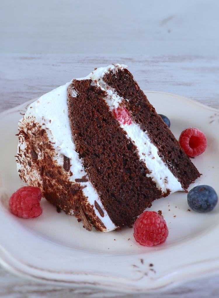 Fatia de bolo de cacau com chantilly e frutos vermelhos num prato