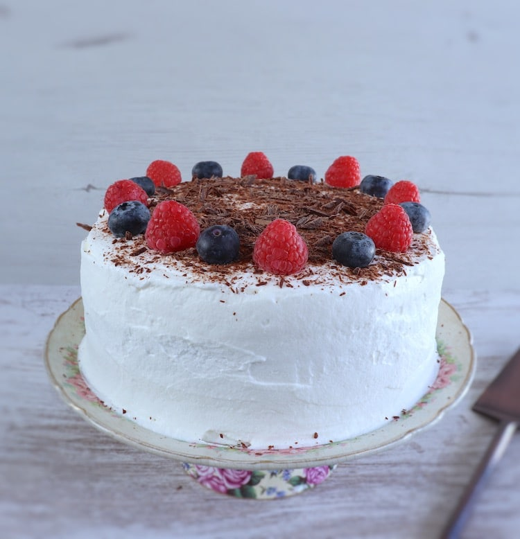 Cocoa cake with whipped cream and berries on a plate