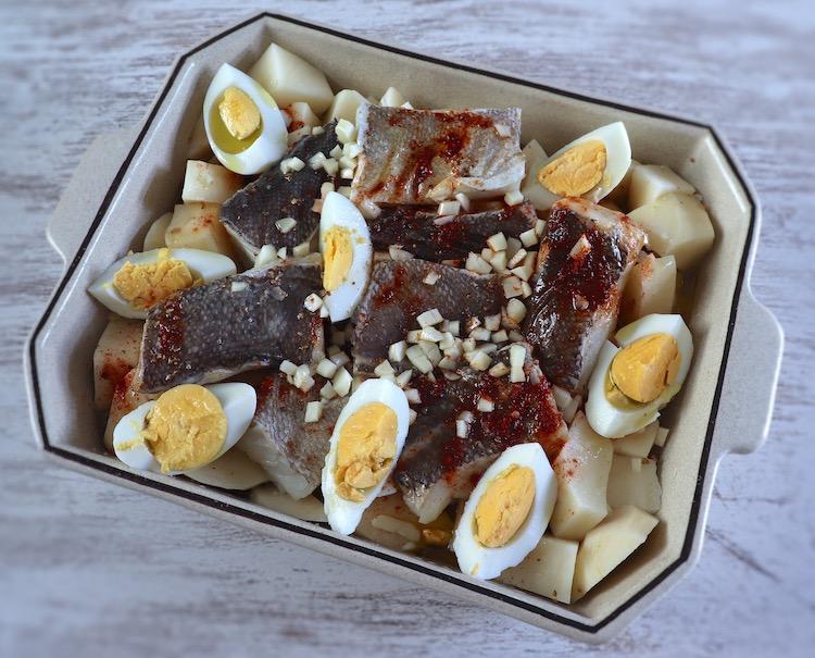 Bacalhau, batatas, cebola, alhos picados, ovos, vinho branco, azeite, pimentão doce, pimenta e sal numa assadeira