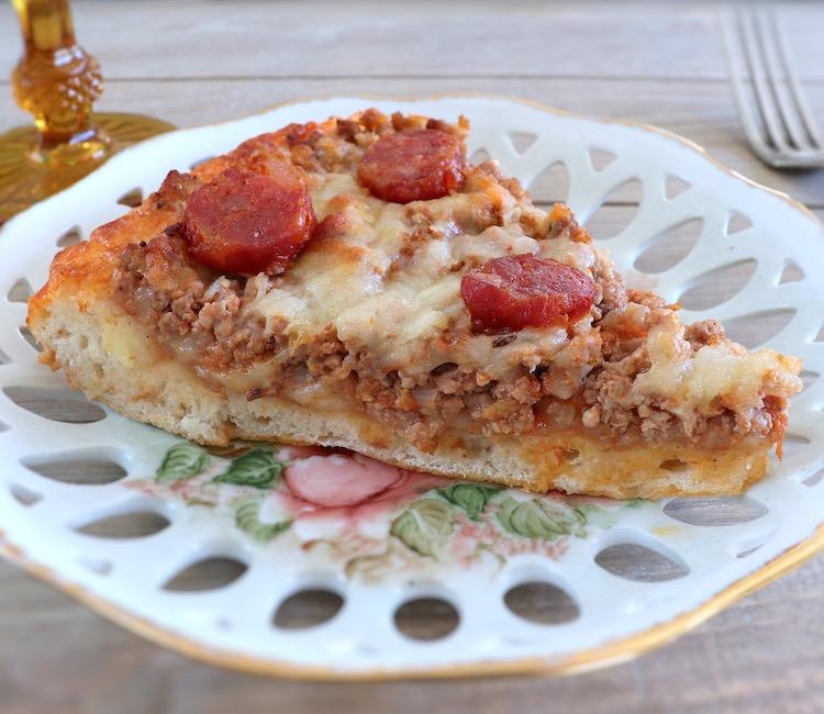 Fatia de pizza de carne e chouriço num prato