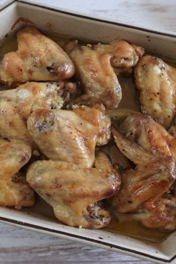 Chicken wings in the oven with olive oil and lemon on a baking dish