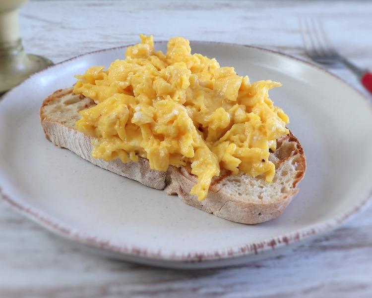 Ovos mexidos com uma fatia de pão num prato
