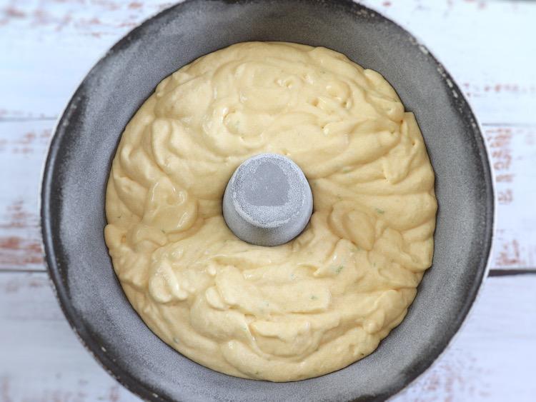 Massa de bolo de lima e iogurte numa forma de bolos redonda com furo no meio