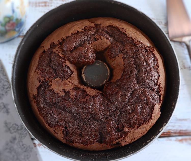 Bolo caseiro de chocolate e morango numa forma de bolos redonda com furo no meio